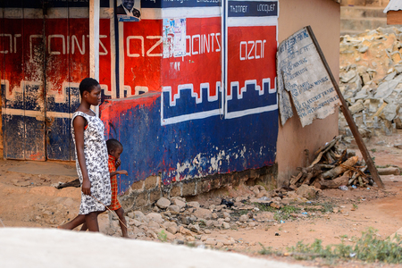 CENTRAL REGION, GHANA - Jan 17, 2017: Unidentified Ghanaian woman and her child walk in local village. People of Ghana suffer of poverty due to the bad economy Editorial