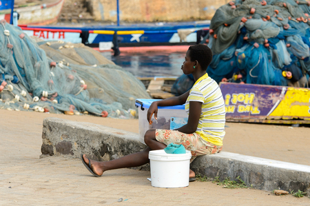 ELMINA, GHANA -JAN 18, 2017: Unidentified  Ghanaian woman rests from work in Elmina port. People of Ghana suffer of poverty due to the bad economy 新聞圖片
