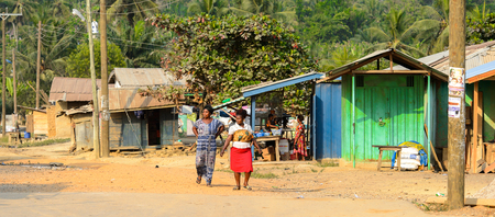 CENTRAL REGION, GHANA - Jan 17, 2017: Unidentified Ghanaian women walk along the street in local village. People of Ghana suffer of poverty due to the bad economy