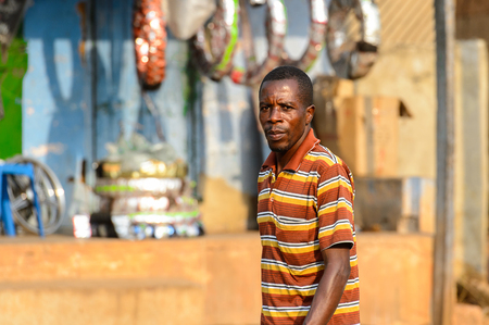 CENTRAL REGION, GHANA - Jan 17, 2017: Unidentified Ghanaian man in striped shirt walks in local village. People of Ghana suffer of poverty due to the bad economy