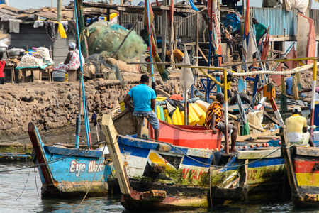 ELMINA, GHANA -JAN 18, 2017: Unidentified  Ghanaian people locate in Elmina port. People of Ghana suffer of poverty due to the bad economy.