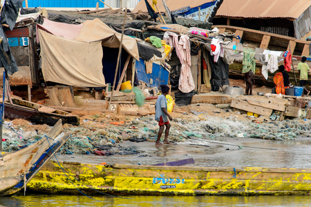 ELMINA, GHANA -JAN 18, 2017: Unidentified  Ghanaian boy walks on the coast of Elmina . People of Ghana suffer of poverty due to the bad economy