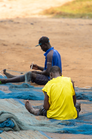 ELMINA, GHANA -JAN 18, 2017: Unidentified  Ghanaian men weave a fishing net on the coast of Elmina. People of Ghana suffer of poverty due to the bad economy