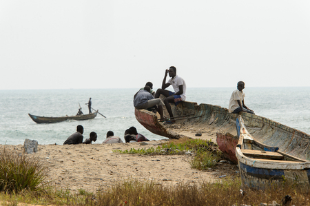 ELMINA, GHANA -JAN 18, 2017: Unidentified  Ghanaian teens hang out on the coast of Elmina. People of Ghana suffer of poverty due to the bad economy Editorial