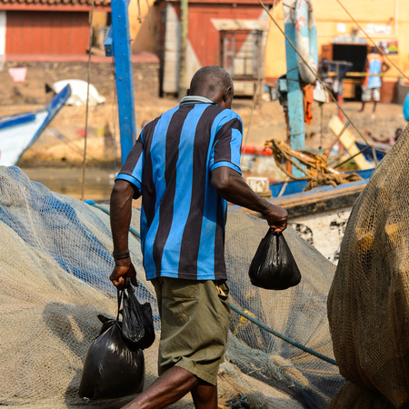 ELMINA, GHANA -JAN 18, 2017: Unidentified  Ghanaian man in striped shirt walks with plastic bags in Elmina port. People of Ghana suffer of poverty due to the bad economy