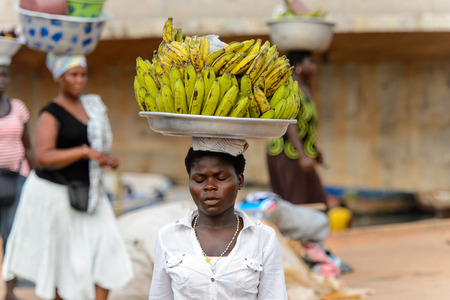 ELMINA, GHANA -JAN 18, 2017: Unidentified  Ghanaian woman carries a tray with bananas  in Elmina port. People of Ghana suffer of poverty due to the bad economy