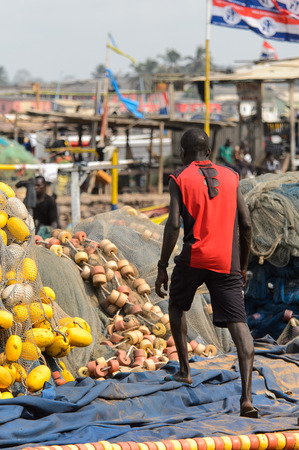 ELMINA, GHANA -JAN 18, 2017: Unidentified  Ghanaian man in red shirt from behind in Elmina port. People of Ghana suffer of poverty due to the bad economy