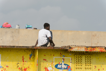 ELMINA, GHANA -JAN 18, 2017: Unidentified  Ghanaian boy sits on the fence in Elmina port. People of Ghana suffer of poverty due to the bad economy 報道画像