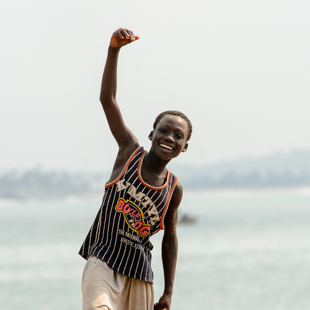 ELMINA, GHANA -JAN 18, 2017: Unidentified  Ghanaian boy raises his hand and smiles on the coast of Elmina. People of Ghana suffer of poverty due to the bad economy 新聞圖片