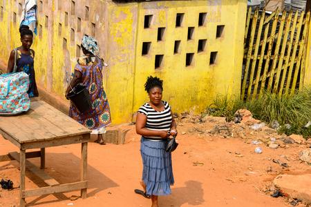 ELMINA, GHANA -JAN 18, 2017: Unidentified  Ghanaian woman walks along the coast of Elmina. People of Ghana suffer of poverty due to the bad economy