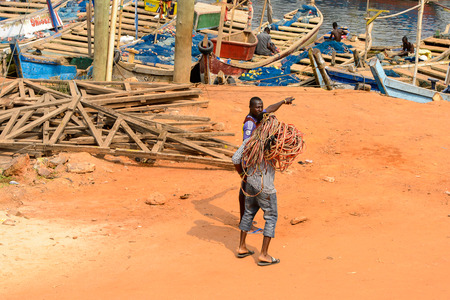 ELMINA, GHANA -JAN 18, 2017: Unidentified  Ghanaian man holds a skein of wire in Elmina. People of Ghana suffer of poverty due to the bad economy Editorial
