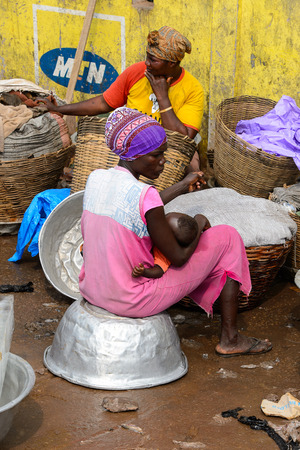 ELMINA, GHANA -JAN 18, 2017: Unidentified  Ghanaian woman sits on the basin in Elmina market. People of Ghana suffer of poverty due to the bad economy