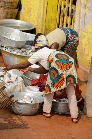 ELMINA, GHANA -JAN 18, 2017: Unidentified  Ghanaian woman bend down to pick something up from basins in Elmina. People of Ghana suffer of poverty due to the bad economy
