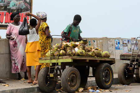 ELMINA, GHANA -JAN 18, 2017: Unidentified  Ghanaian boy chops coconuts on the cart in Elmina. People of Ghana suffer of poverty due to the bad economy
