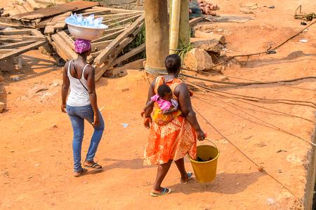 ELMINA, GHANA -JAN 18, 2017: Unidentified  Ghanaian people walk along the coast of Elmina. People of Ghana suffer of poverty due to the bad economy
