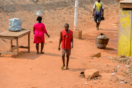 ELMINA, GHANA -JAN 18, 2017: Unidentified  Ghanaian woman carries a basin on the street in Elmina. People of Ghana suffer of poverty due to the bad economy Stock Photo - 112792175