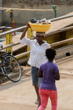 ELMINA, GHANA -JAN 18, 2017: Unidentified  Ghanaian woman carries a basin on her head in Elmina port. People of Ghana suffer of poverty due to the bad economy.