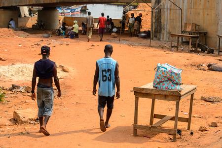 ELMINA, GHANA -JAN 18, 2017: Unidentified  Ghanaian men walk along the port of Elmina. People of Ghana suffer of poverty due to the bad economy
