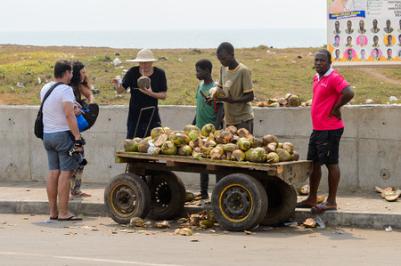 ELMINA, GHANA -JAN 18, 2017: Unidentified  Ghanaian boy chops and sells coconuts on the cart in Elmina port. People of Ghana suffer of poverty due to the bad economy