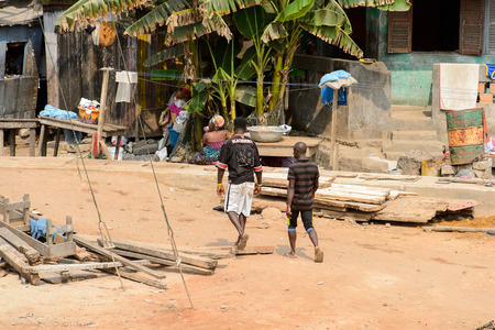 ELMINA, GHANA -JAN 18, 2017: Unidentified  Ghanaian men walk along the shore of Elmina port. People of Ghana suffer of poverty due to the bad economy