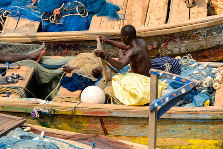 ELMINA, GHANA -JAN 18, 2017: Unidentified  Ghanaian man weaves fishing net on the boat in Elmina port. People of Ghana suffer of poverty due to the bad economy Editorial