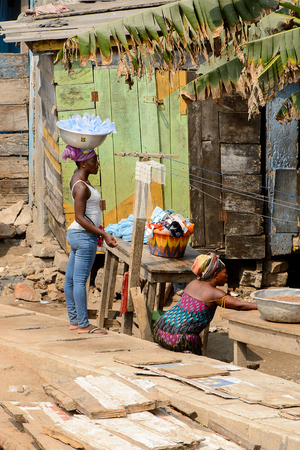 ELMINA, GHANA -JAN 18, 2017: Unidentified  Ghanaian woman carries a basin on her head on the shore of Elmina port. People of Ghana suffer of poverty due to the bad economy