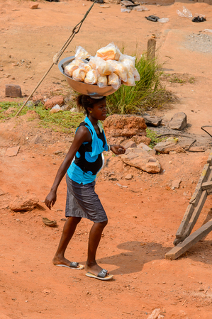 ELMINA, GHANA -JAN 18, 2017: Unidentified  Ghanaian woman carries a basin with bread on her head in Elmina. People of Ghana suffer of poverty due to the bad economy 報道画像