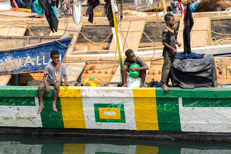 ELMINA, GHANA -JAN 18, 2017: Unidentified  Ghanaian boys stand on the boat in Elmina port. People of Ghana suffer of poverty due to the bad economy
