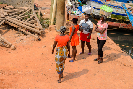ELMINA, GHANA -JAN 18, 2017: Unidentified  Ghanaian woman in red shirt from behind in Elmina. People of Ghana suffer of poverty due to the bad economy