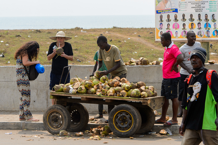 ELMINA, GHANA -JAN 18, 2017: Unidentified  Ghanaian boy chops coconuts on the cart in Elmina port. People of Ghana suffer of poverty due to the bad economy