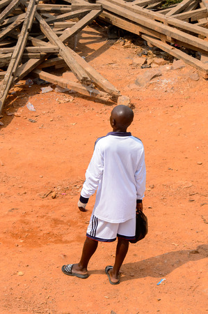 ELMINA, GHANA -JAN 18, 2017: Unidentified  Ghanaian man walks along the road in Elmina. People of Ghana suffer of poverty due to the bad economy.
