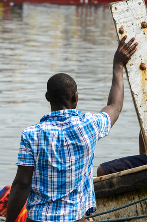 ELMINA, GHANA -JAN 18, 2017: Unidentified  Ghanaian man holds a wooden board near the boat in Elmina port. People of Ghana suffer of poverty due to the bad economy