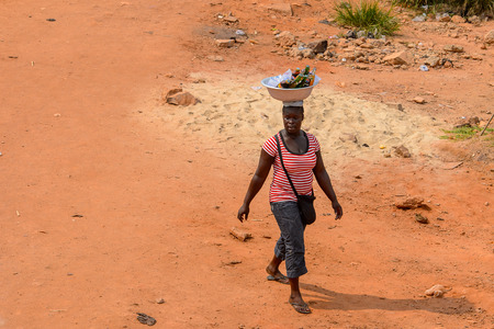 ELMINA, GHANA -JAN 18, 2017: Unidentified  Ghanaian woman carries a basin on her head on the coast of Elmina. People of Ghana suffer of poverty due to the bad economy