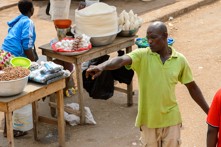 ELMINA, GHANA -JAN 18, 2017: Unidentified  Ghanaian man in green shirt points on something in Elmina port. People of Ghana suffer of poverty due to the bad economy