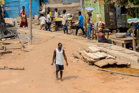 ELMINA, GHANA -JAN 18, 2017: Unidentified  Ghanaian man in white shirt walks along the road in Elmina port. People of Ghana suffer of poverty due to the bad economy 新聞圖片