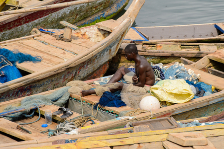 ELMINA, GHANA -JAN 18, 2017: Unidentified  Ghanaian man sits on the boat in Elmina port. People of Ghana suffer of poverty due to the bad economy