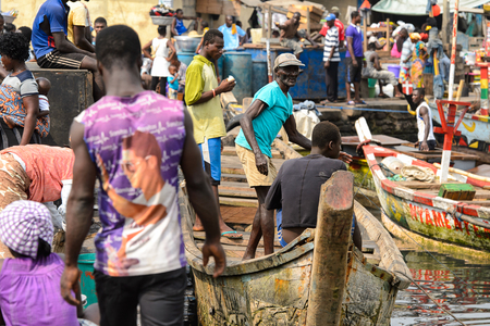 ELMINA, GHANA -JAN 18, 2017: Unidentified  Ghanaian men in boat in Elmina port. People of Ghana suffer of poverty due to the bad economy Editorial
