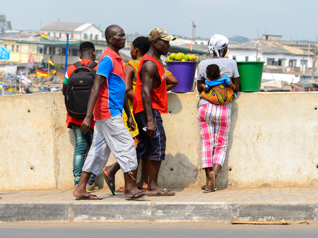 ELMINA, GHANA -JAN 18, 2017: Unidentified  Ghanaian people near the fence in Elmina. People of Ghana suffer of poverty due to the bad economy