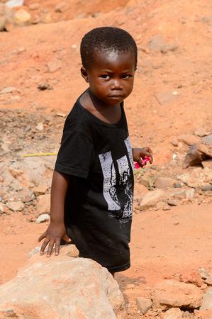 ELMINA, GHANA -JAN 18, 2017: Unidentified  Ghanaian little boy in black shirt walks on the street in Elmina. Children of Ghana suffer of poverty due to the bad economy
