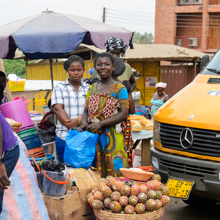 CENTRAL REGION, GHANA - Jan 17, 2017: Unidentified Ghanaian women stand near the basin with pineapples in local village. People of Ghana suffer of poverty due to the bad economy