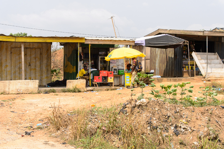 CENTRAL REGION, GHANA - Jan 17, 2017: Unidentified Ghanaian woman sells food under yellow umbrella in local village. People of Ghana suffer of poverty due to the bad economy