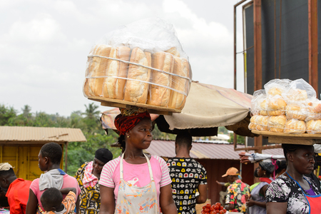 CENTRAL REGION, GHANA - Jan 17, 2017: Unidentified Ghanaian woman carries a tray with bread in local village. People of Ghana suffer of poverty due to the bad economy