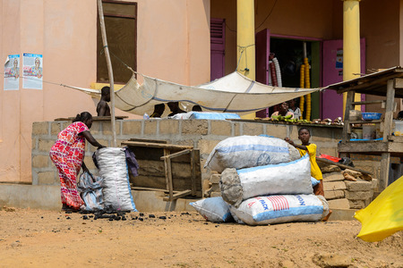 CENTRAL REGION, GHANA - Jan 17, 2017: Unidentified Ghanaian woman holds for the bag in local village. People of Ghana suffer of poverty due to the bad economy