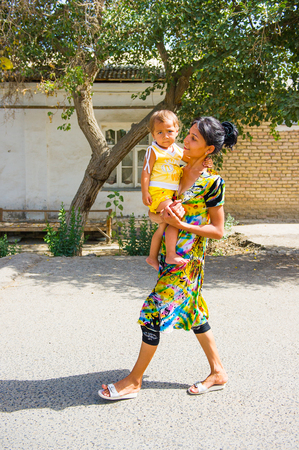 BUKHARA, UZBEKISTAN - JUNE 7, 2011: Unidentified Uzbek woman goes for a walk with her child Uzbekistan, Jun 7, 2011.  81% of people in Uzbekistan belong to Uzbek ethnic group