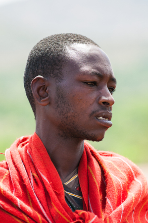 AMBOSELI, KENYA - OCTOBER 10, 2009: Portrait of an unidentified Massai man in red typical tribal clothes in Kenya, Oct 10, 2009. Massai people are a Nilotic ethnic group Standard-Bild - 113977849