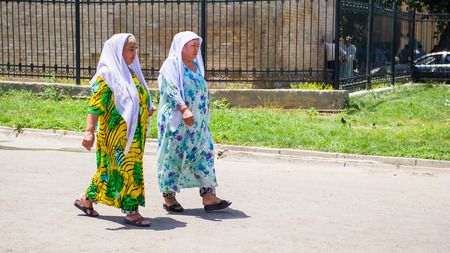 SAMARKAND, UZBEKISTAN - JUNE 10, 2011: Two unidentified Uzbek women walk in the garden in Uzbekistan, Jun 10, 2011.  81% of people in Uzbekistan belong to Uzbek ethnic group