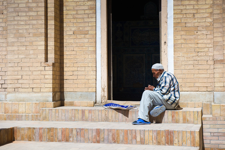 KHIVA, UZBEKISTAN - JUNE 4, 2011: Unidentified Uzbek man sits and thinks on a porch in Uzbekistan. 81% of people in Uzbekistan belong to Uzbek ethnic group