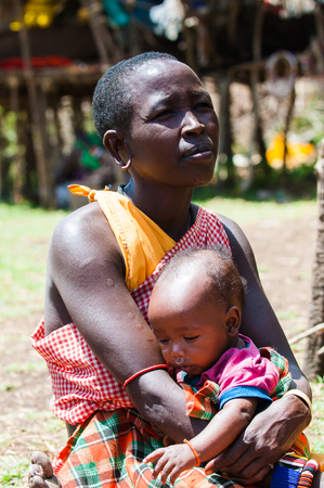 AMBOSELI, KENYA - OCTOBER 10, 2009: Unidentified Massai woman give a hug of love to her little child in Kenya, Oct 10, 2009. Massai people are a Nilotic ethnic group