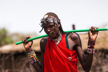 Kenia - 10. Oktober 2009: Nicht identifizierte Massai-Frau geht in typischer roter Stammeskleidung und trägt einen Rocker für Wasser in Kenia, 10. Oktober 2009. Massai sind eine nilotische ethnische Gruppe