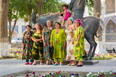 BUKHARA, UZBEKISTAN - JUNE 6, 2011: Group of Unidentified Uzbek women take picture near a monument in Uzbekistan, Jun 6, 2011.  81% of people in Uzbekistan belong to Uzbek ethnic group Editorial